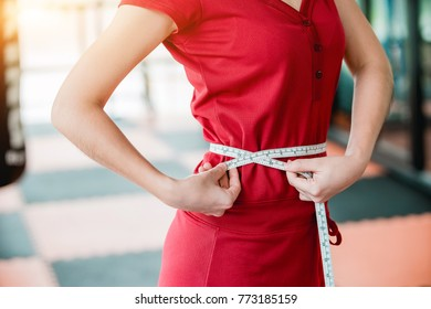 A young woman wearing a workout in the fitness center are using waist measurement cables yourself.