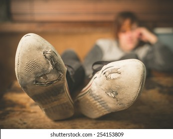 A young woman wearing worn out shoes is resting her feet on a table at home