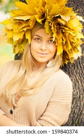 young woman wearing a wreath of autumn leaves