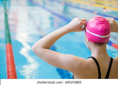 young woman wears glasses in front of the swimming pool. Back.