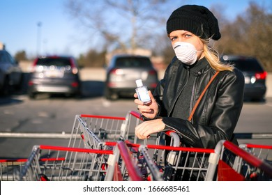 A young woman wears an N95 respirator mask and holds up a bottle of hand sanitizer after going shopping to stock up food and supplies in wake of the coronavirus epidemic in the United States.