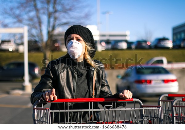 A young woman wears an N95 respirator mask while pushing a shopping cart outside of a grocery store. The woman is protecting herself from coronavirus and other airborne particles and diseases.