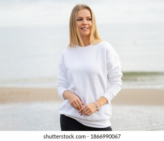 Young woman wears white blouse in summer or autumn time. Blond woman stands in front of camera on beach, outdoor. Fashion mockup with copy space.  Sweatshirt template.