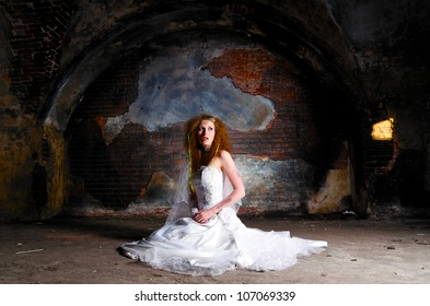 young woman in wedding dress at abandoned place