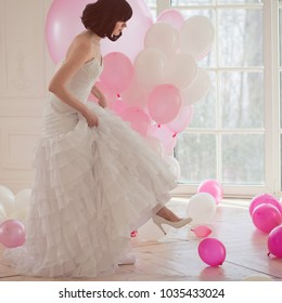 Young woman in wedding dress in luxury interior with a mass of pink and white balloons, sitting on the floor. Hold in hands her white shoes. Charming young bride brunette with short haircut
