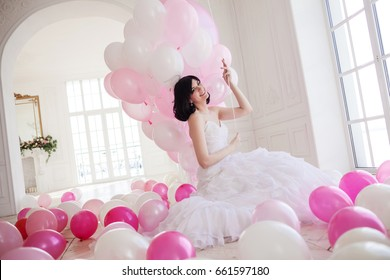 Young woman in wedding dress in luxury interior with a mass of pink and white balloons.
