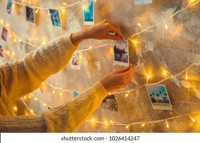 Young woman weekend at home decorated bedroom sticking photo