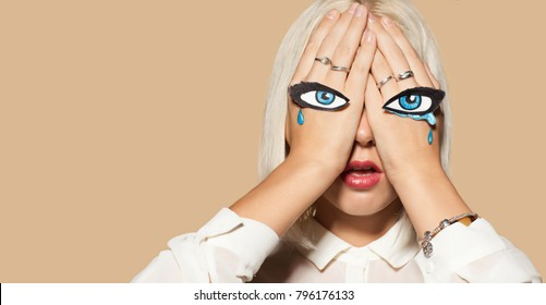 Young woman weeping with eyes painted on her hands. Studio portrait of beautiful blonde model with tears on eyes. Emotion of despair and sorrow. Beige wall on background.