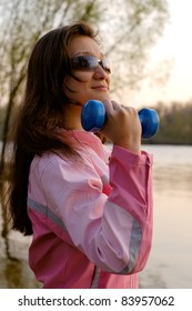 Young woman with weights exercising in the nature Healthy lifestyle and fitness concept