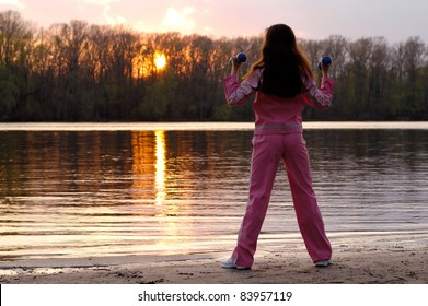 Young woman with weights exercising in the nature in sunset near the river Healthy lifestyle and fitness concept