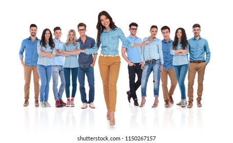 young woman welcomes you in her casual team with both hands and a smile while standing on white background