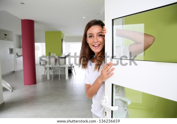 Young woman welcoming people at entrance door