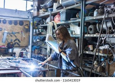 young woman welding in a workshop
