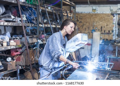 young woman welding in workshop