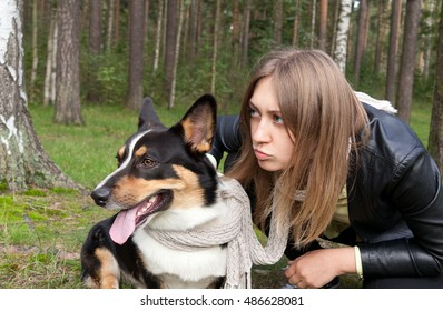 Young woman and Welsh Corgi Cardigan carefully looking into the distance