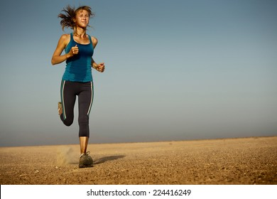 Young woman in wet clothes running in the desert