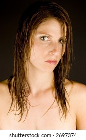 A young woman with wet hair against a plain background.