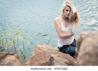 Young woman in wet T-shirt resting on the seashore
