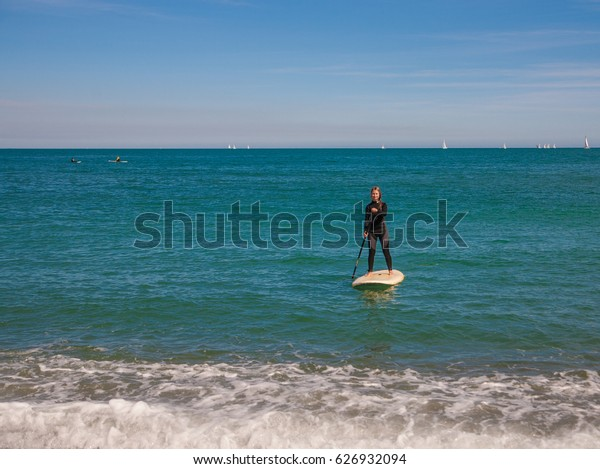 Young woman in wetsuit swim on stand up paddle board