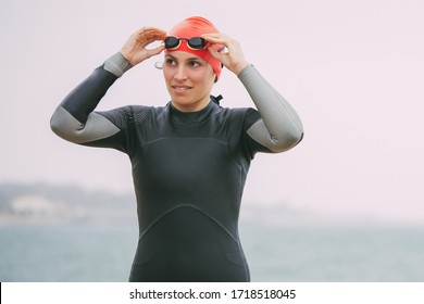 Young woman in wetsuit wearing goggles. Female swimmer wearing sportswear and protective glasses near body of water at cloudy day. Triathlon concept