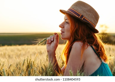 Young woman in the wheat field at the sunset