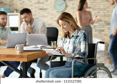 Young woman in wheelchair and colleagues at workplace