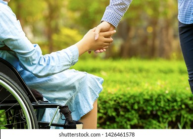 Young woman in wheelchair holding hands with caretaker man in public park.