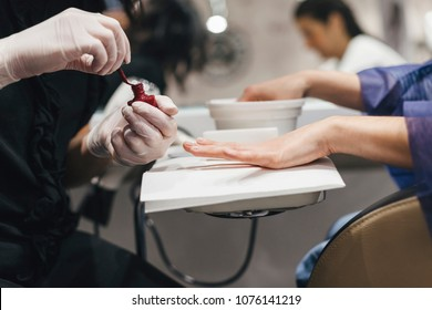 Young woman while applying red nail polish during a manicure by the beautician