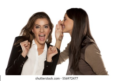 young woman whispered good news to her friend