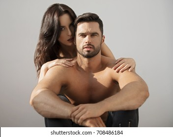 Young woman whispering in the ear of her boyfriend