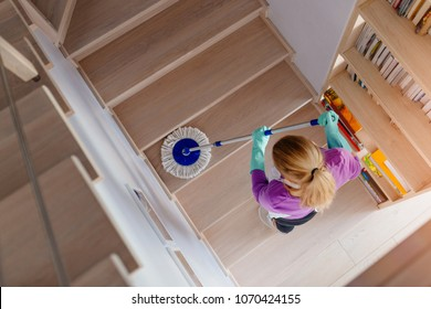 Young woman in white apron cleaning stairs. Cleaning service. Maid cleaning at home