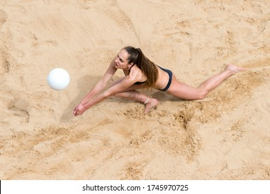 Young woman with white ball playing volleyball on beach. Summer vacation and sport concept