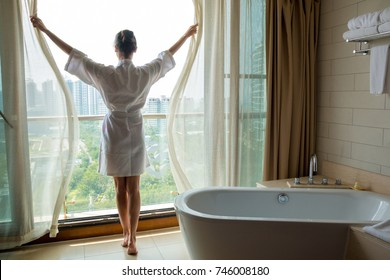 Young woman in white bathrobe opening window in luxury bathroom with city view