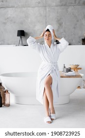 Young woman in white bathrobe and towel sitting with closed eyes on bathtub