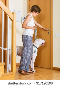 Young woman with white big dog on leash staying at door