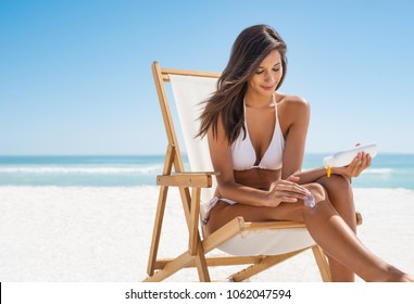 7095f1b90b5e1 Young woman in white bikini applying suntan lotion while sitting on  deckchair. Smiling latin girl