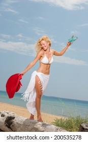 Young woman in white bikini holding sarong on windy beach