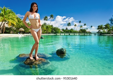 Young woman in white bikini standing next to tropical beach