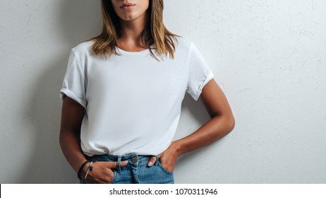 Young woman in white blank t-shirt, grunge wall, studio close-up