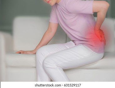 young woman in white clothes sitting on sofa, grabbing an Waist, She has Waist pain. Waist pain And Care Concept.