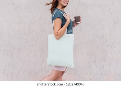Young woman with white cotton bag and paper coffee cup in her hands.