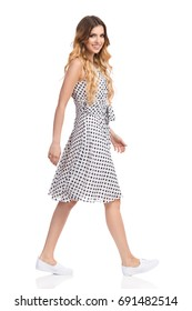 Young woman in white dotted dress, sneakers is walking, looking at camera and smiling. Side view. Full length studio shot isolated on white.