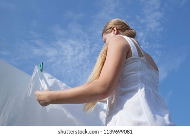 Young woman in white dress with clean sheets outdoors. Girl teenager fixing them with clothespins. Rear view against the blue sky