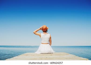 Young woman in white dress enjoy summer near ocean