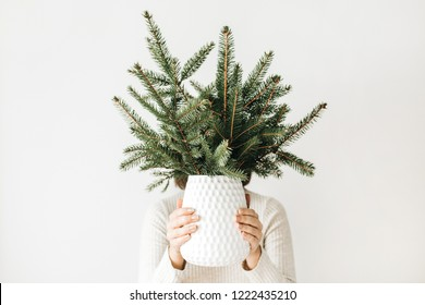 Young woman in white dress holding vase with fir branches bouquet. Winter / New Year / Christmas concept.