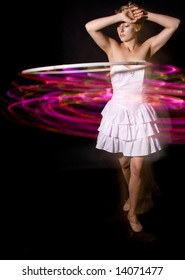 Young woman in white dress hula-hooping against a black background with LED hoop.