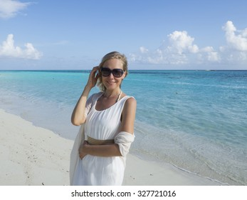 A young woman in a a white dress is posing on a beach in the Maldives.