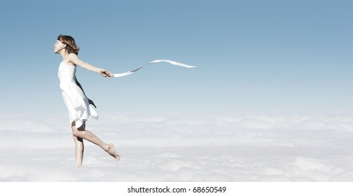 Young woman in white dress with white ribbon walking in a clouds