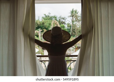 Young woman in white dress and round hat opening the curtain in the room of a hotel with jungle view during her luxury vacation in Bali, Asia