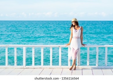 Young woman in white dress, sea and bright sky in the background
